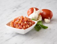 Bruschetta in small bowl, with tomatoes, garlic, and basil in background